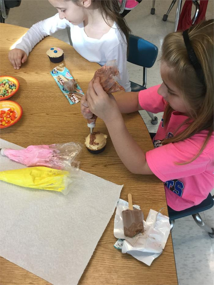 Mrs. Rookard's first grade class decorated cupcakes to go with the story they have been reading called A Cupcake Party.